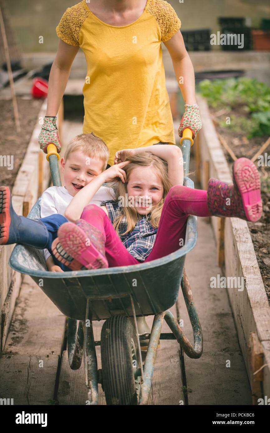 Mother having fun with kids in wheelbarrow - Stock Image