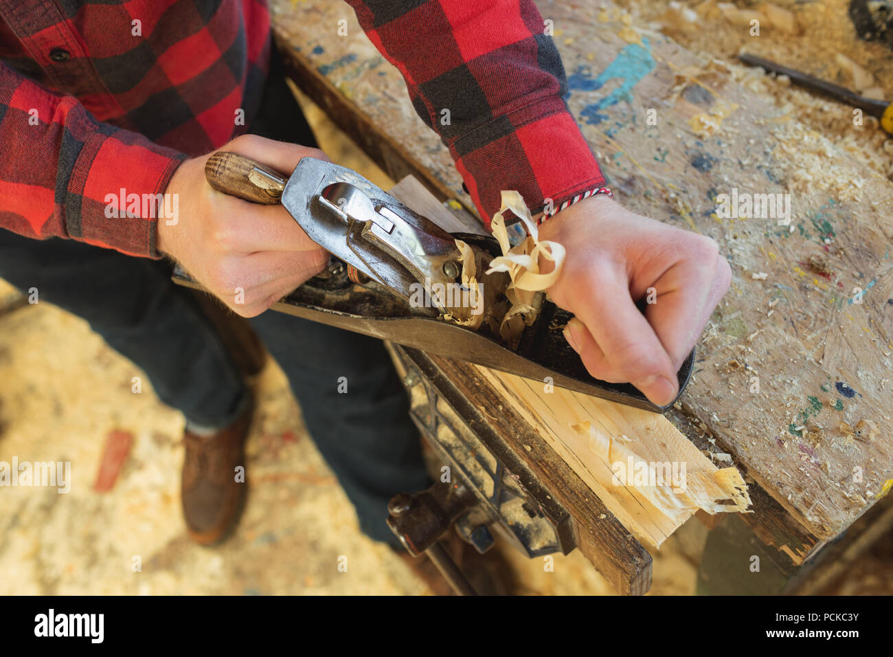 Male carpenter using plane tool in workshop - Stock Image