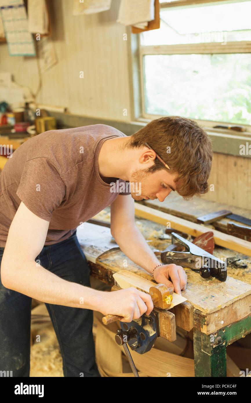 Male carpenter using marking gauge in workshop - Stock Image