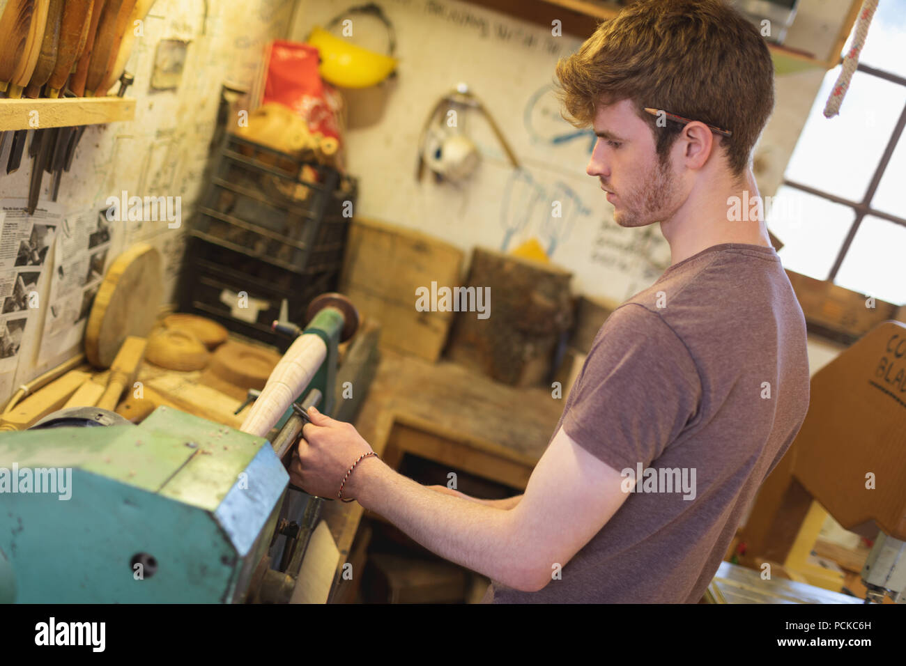 Male carpenter sharping tool on machine - Stock Image
