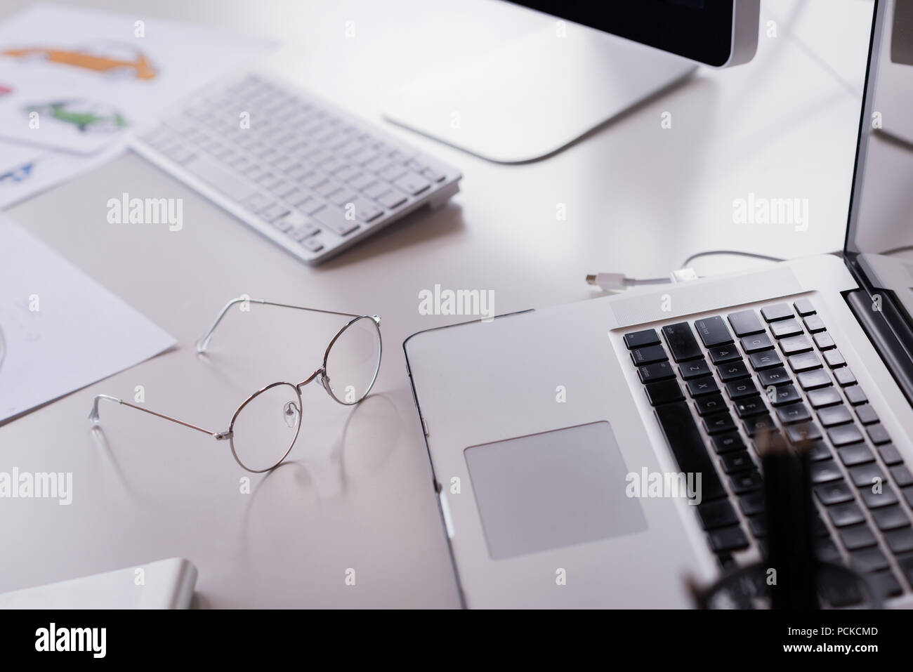 Laptop, computer keyword, spectacles and documents on office table - Stock Image