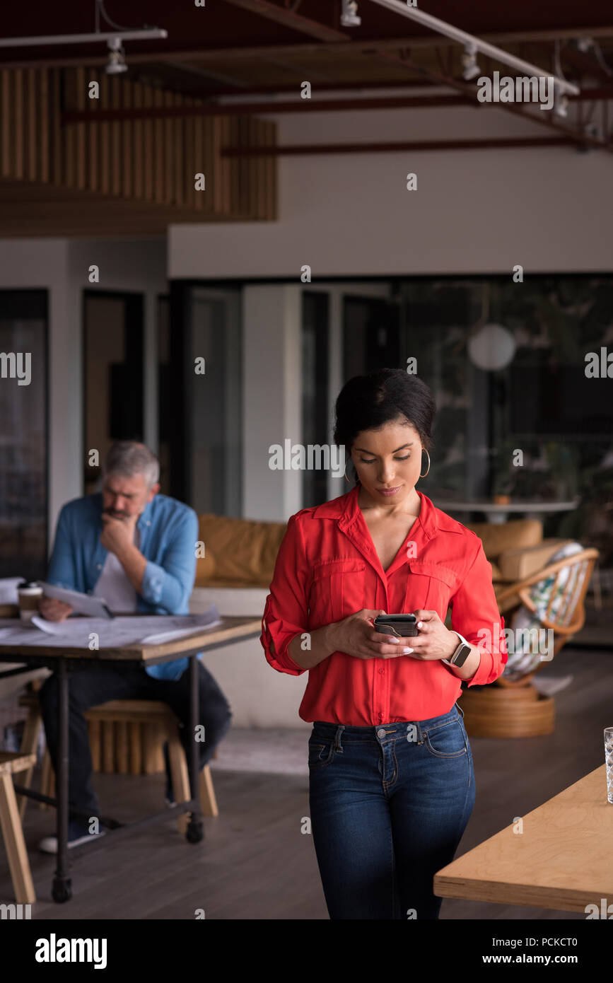 Office executive using mobile phone at creative office Stock Photo