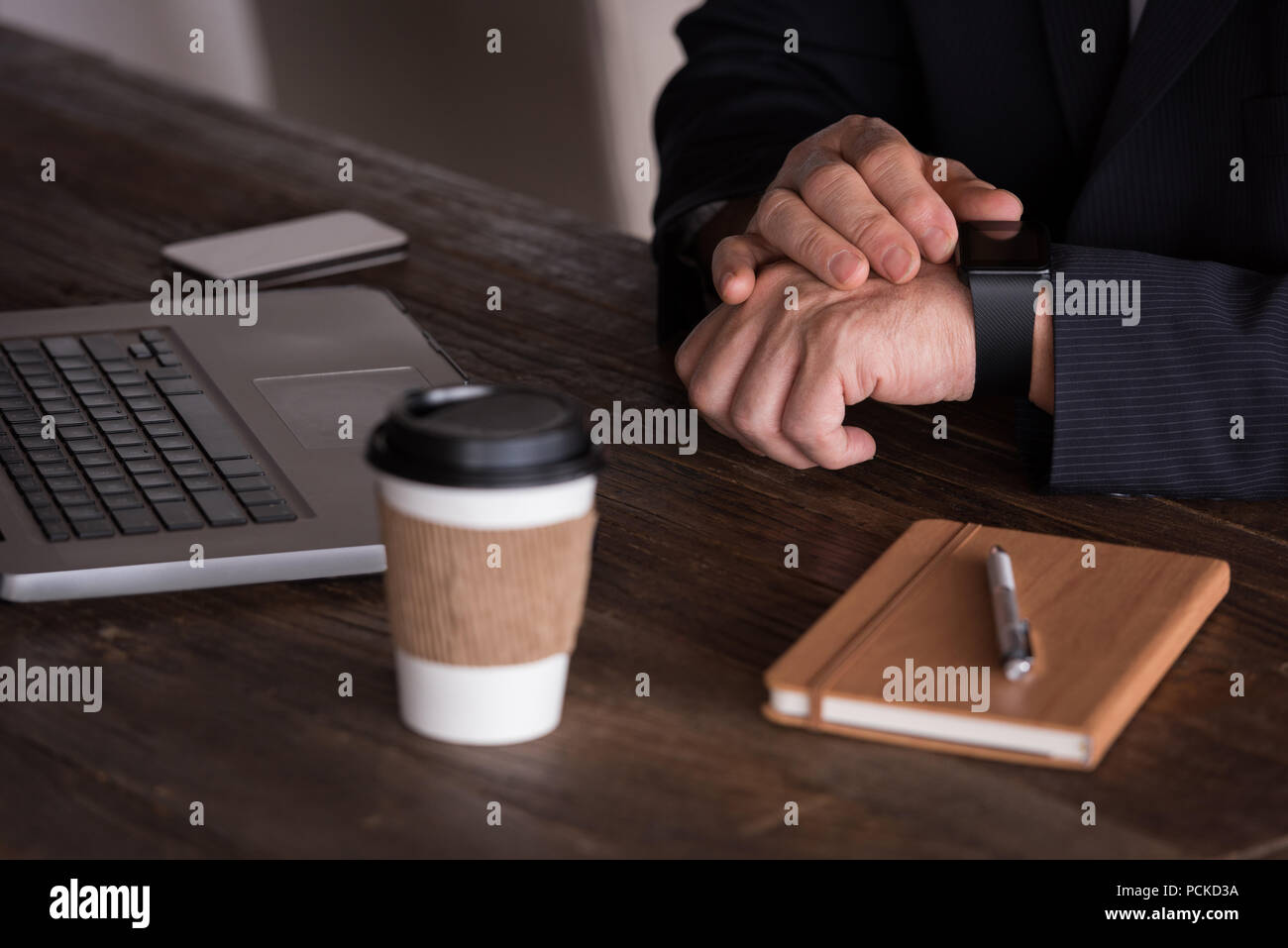 Businessman checking smart watch in creative office - Stock Image