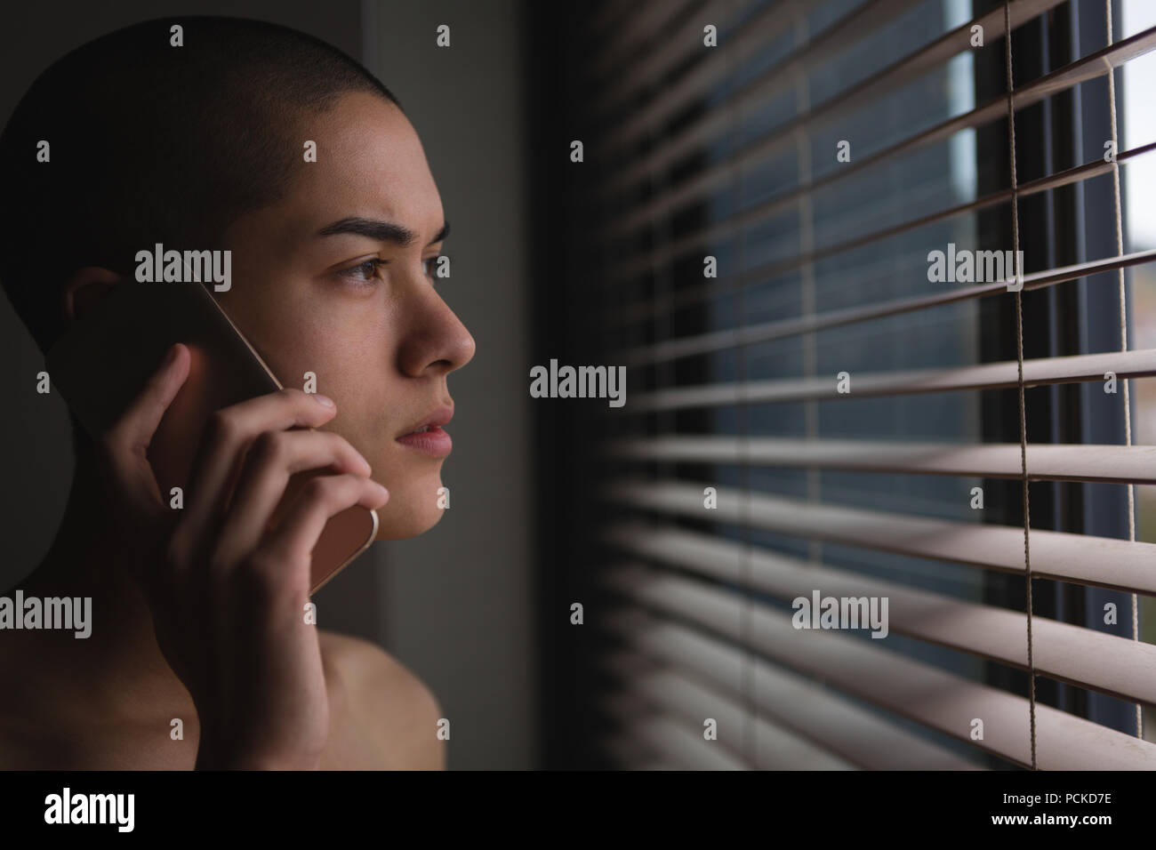 Young man talking on mobile phone while looking through window - Stock Image