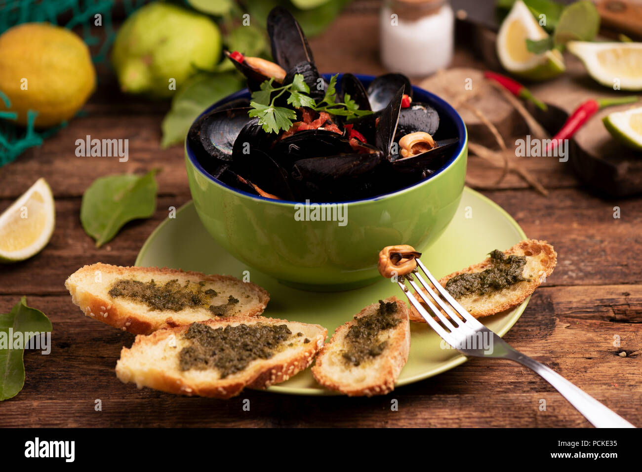 Boiled mussels in cooking dish on wooden background Stock Photo