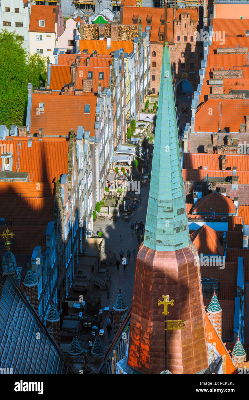 Poland Baltic city, aerial view of typical tall terraced houses in Ulica Mariacka in Gdansk Old Town with a spire of St Mary's Church in foreground. - Stock Image
