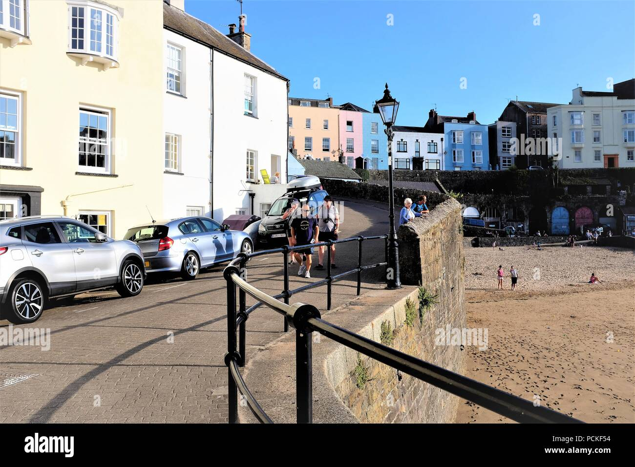 Tenby, Pembrokeshire, South Wales, UK, July 23, 2018.  Holidaymakers walking the  entrance to the pcturesque harbor quay at Tenby in South Wales, UK. Stock Photo