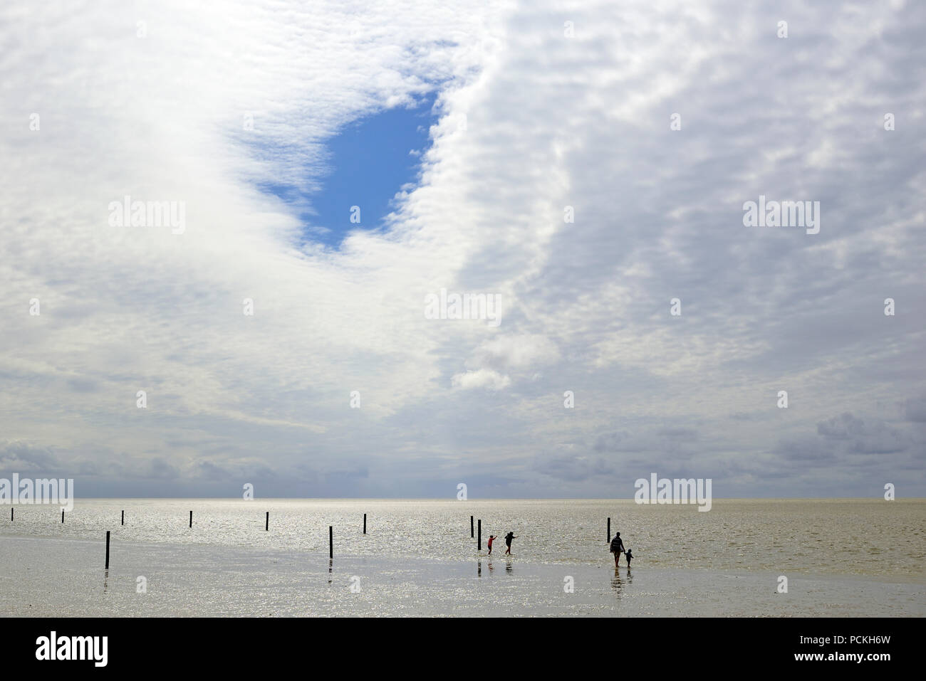 Persons in intertidal zone at rising Water, Norddeich, North Sea, Lower Saxony, Germany Stock Photo