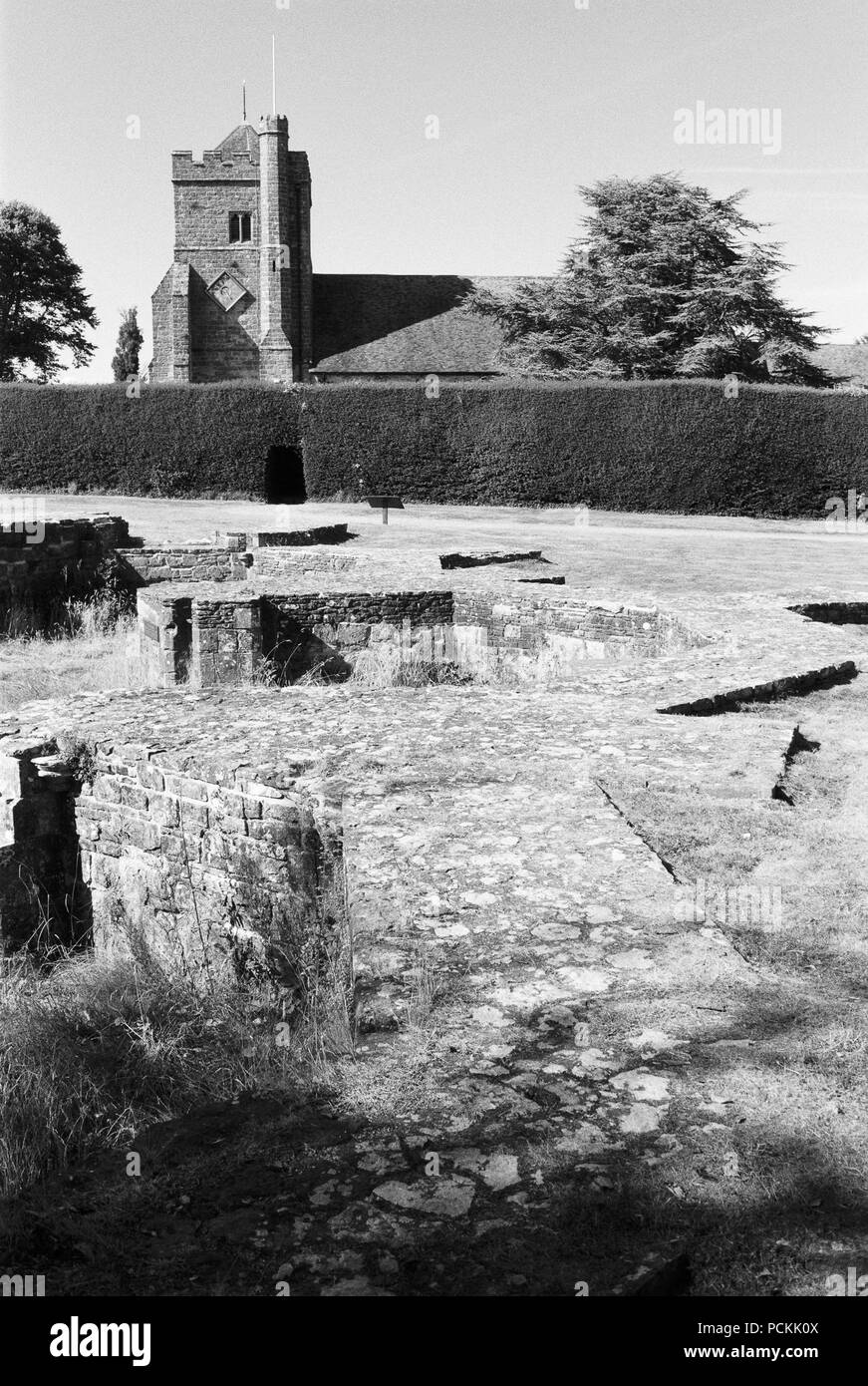 Remains of part of Battle Abbey, East Sussex, UK, with St Mary's church outside the grounds in the background - Stock Image