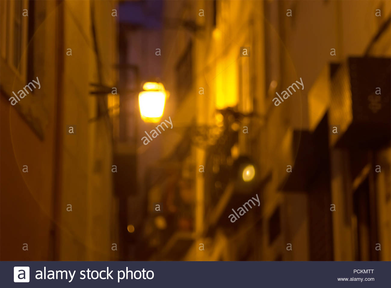 The lantern shines at night on a small street. Lisbon, Portugal Stock Photo