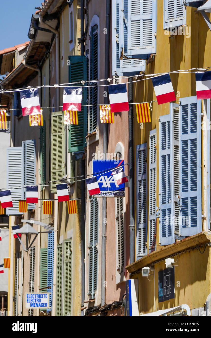 Pedestrian street overall dressed with flags, Saint-Maximin la Sainte-Baume, Var, France - Stock Image