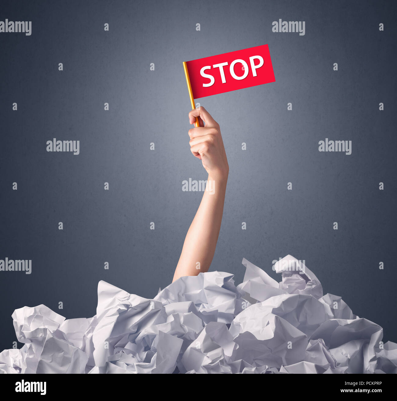 Female hand emerging from crumpled paper pile holding a red flag with stop written on it  - Stock Image
