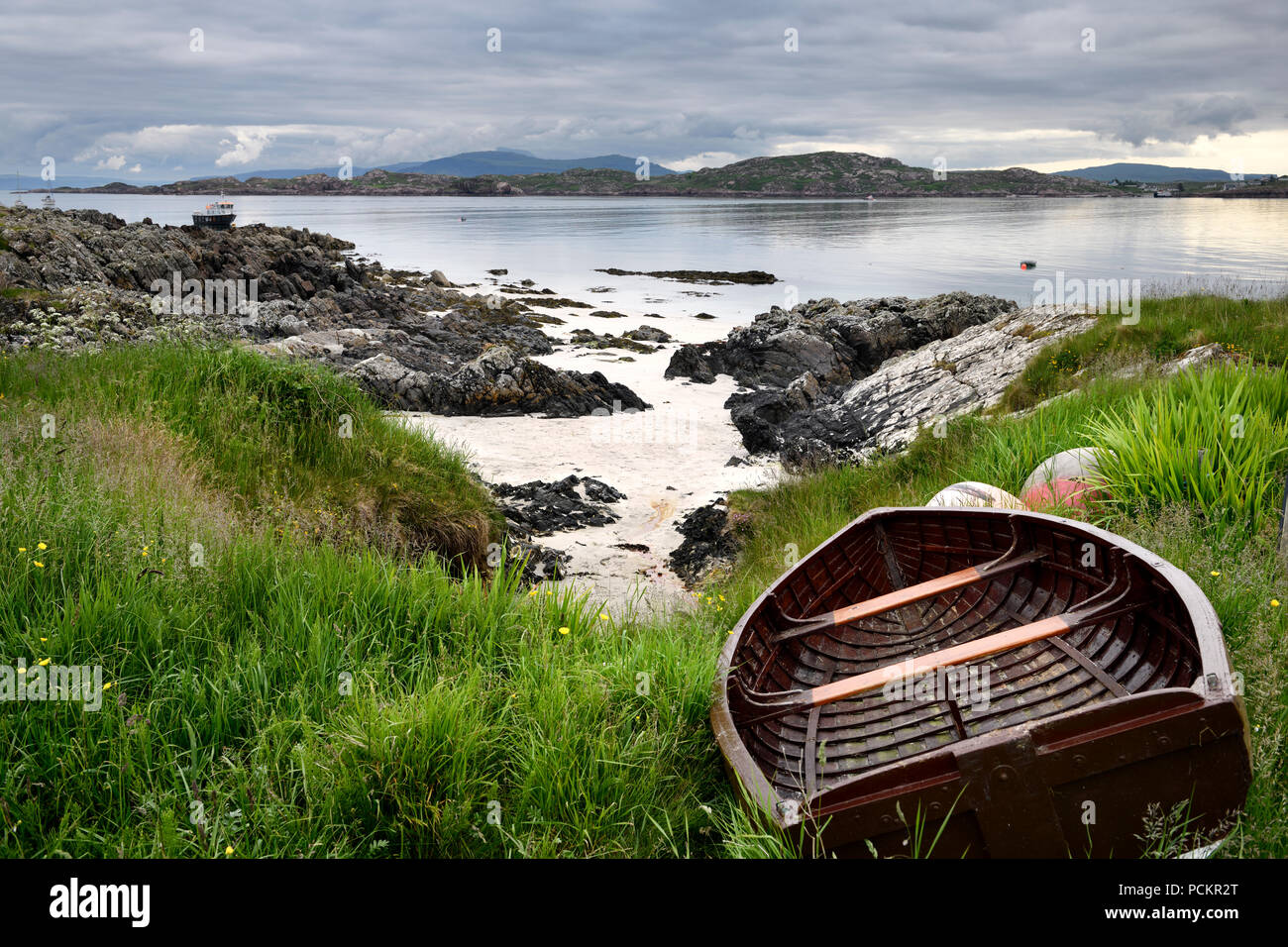 Rocky shore of Isle of Iona with beached boat with Fionnphort Isle of Mull and mountains of Ben More past Sound of Iona Inner Hebrides Scotland UK - Stock Image