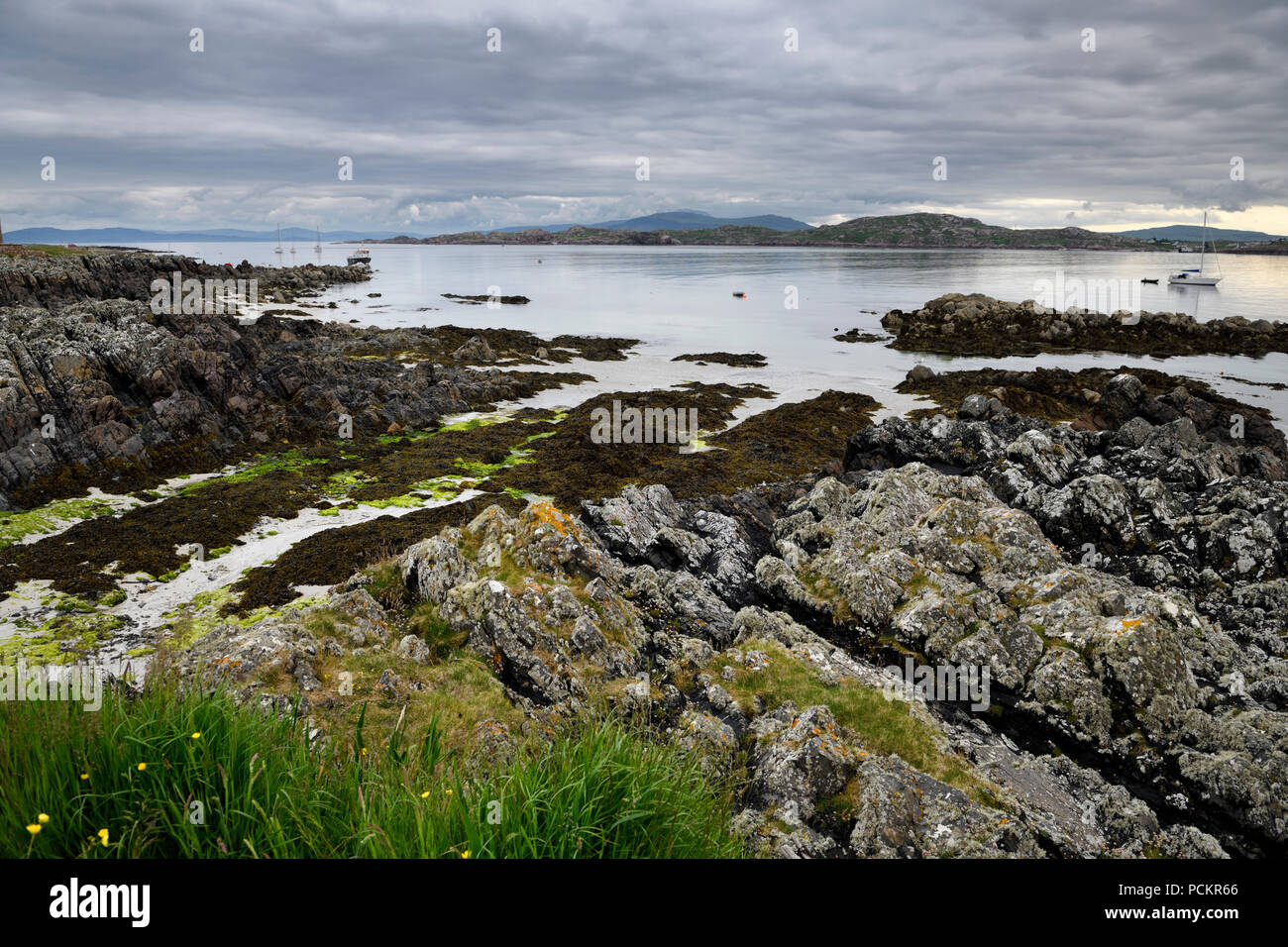 Sand beach and rocky shore under clouds on Isle of Iona with boats on Sound of Iona and Fionnphort Isle of Mull mountains Scotland UK - Stock Image