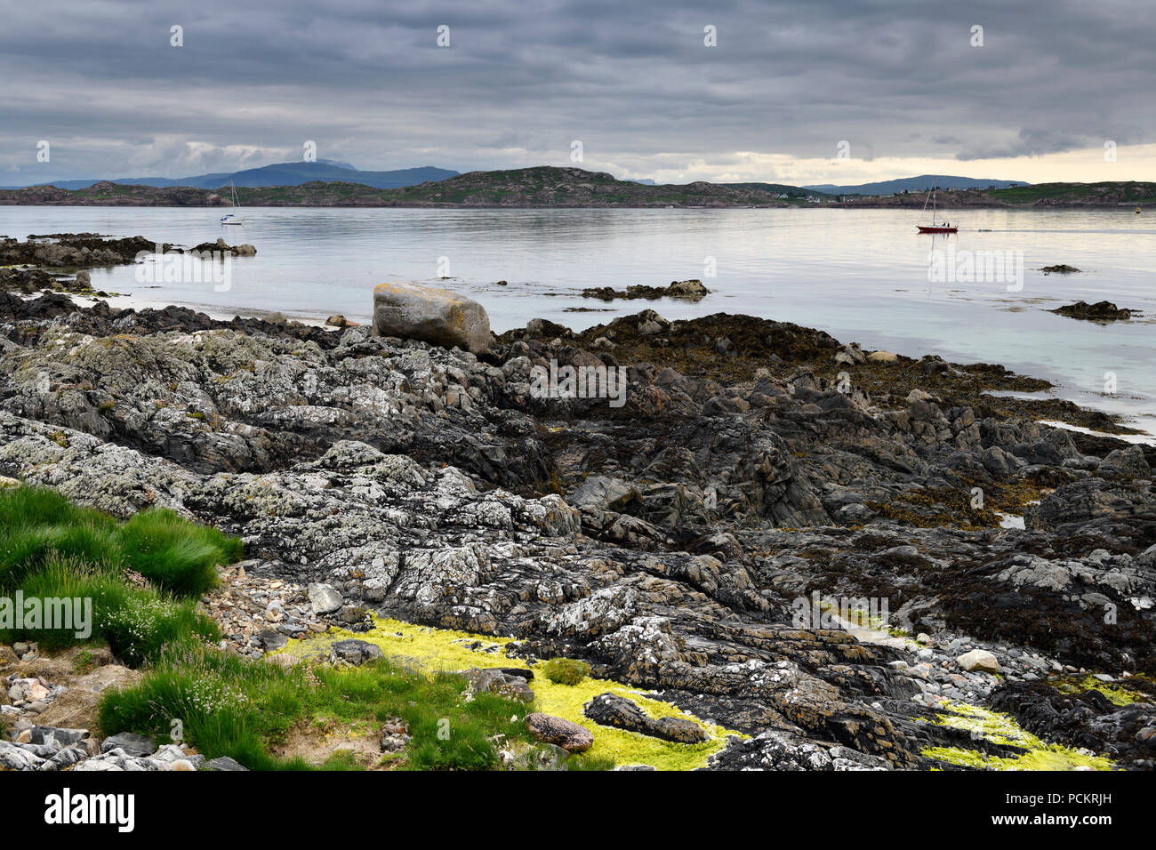 Rocky shore of Isle of Iona with sailboats on Sound of Iona and view of Fionnphort Isle of Mull mountains Inner Hebrides Scotland UK - Stock Image