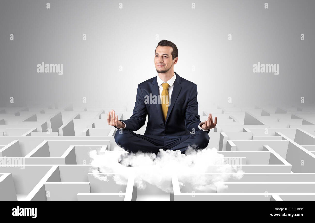 Young businessman meditate in yoga position on a cloud with infinity maze concept  - Stock Image