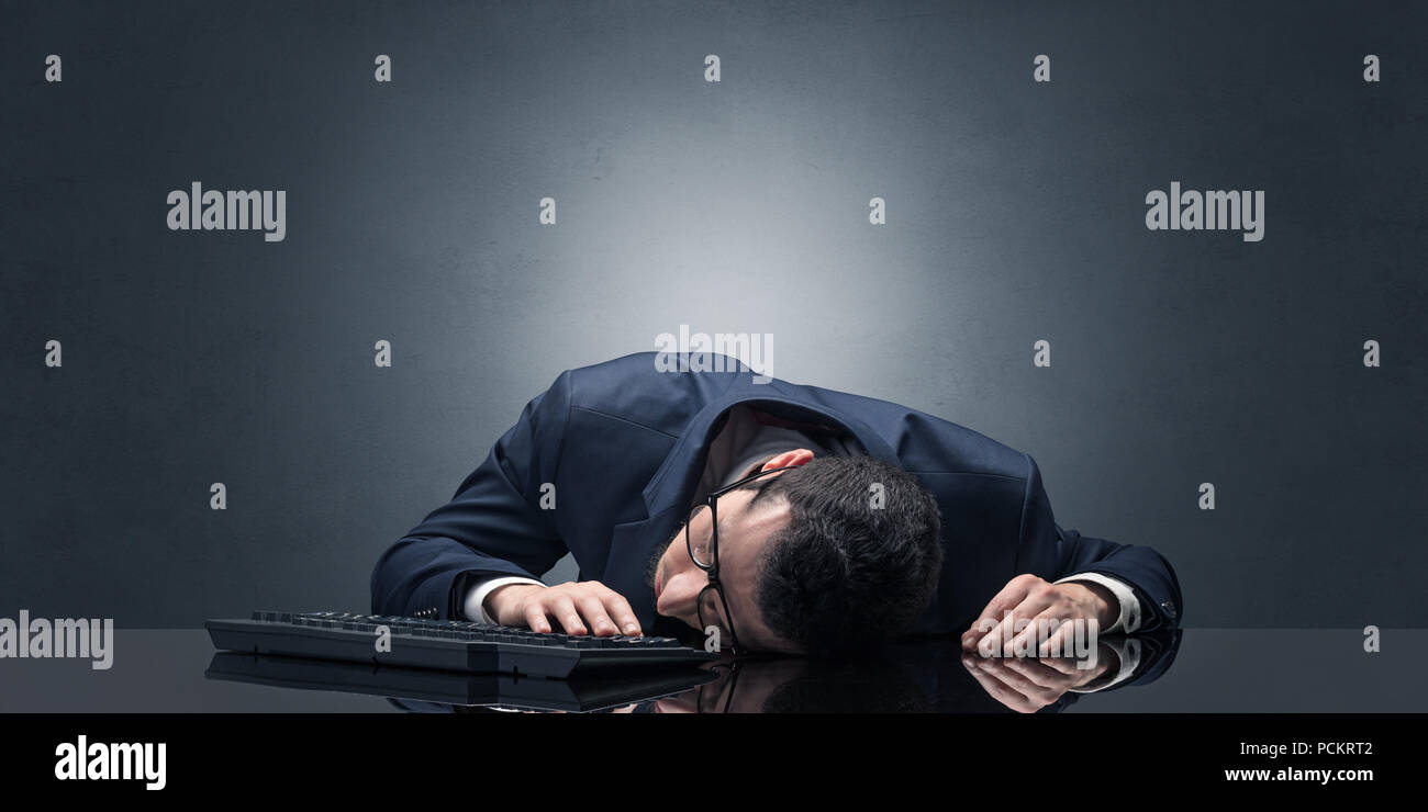 Young businessman fell asleep at his workplace with copy space - Stock Image
