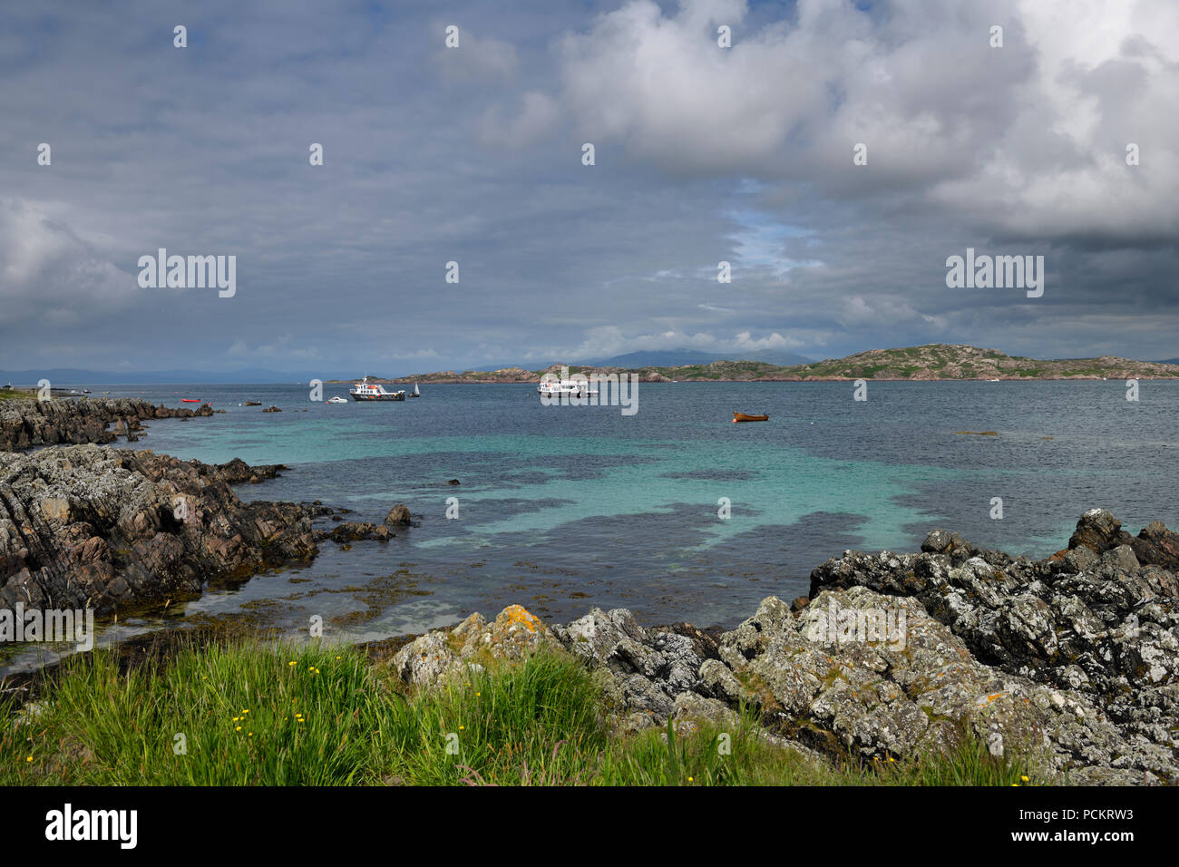 Rocky shore of Isle of Iona looking at Isle of Mull and mountains of Ben More and tour boats in Sound of Iona Inner Hebrides Scotland UK - Stock Image