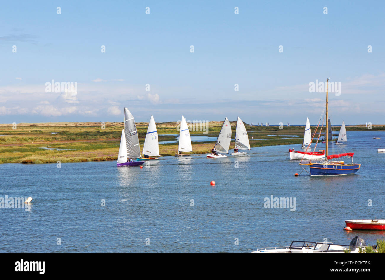 A group of sailing dinghies in Overy Creek heading in on a high tide to Burnham Overy Staithe, Norfolk, England, United Kingdom, Europe. - Stock Image