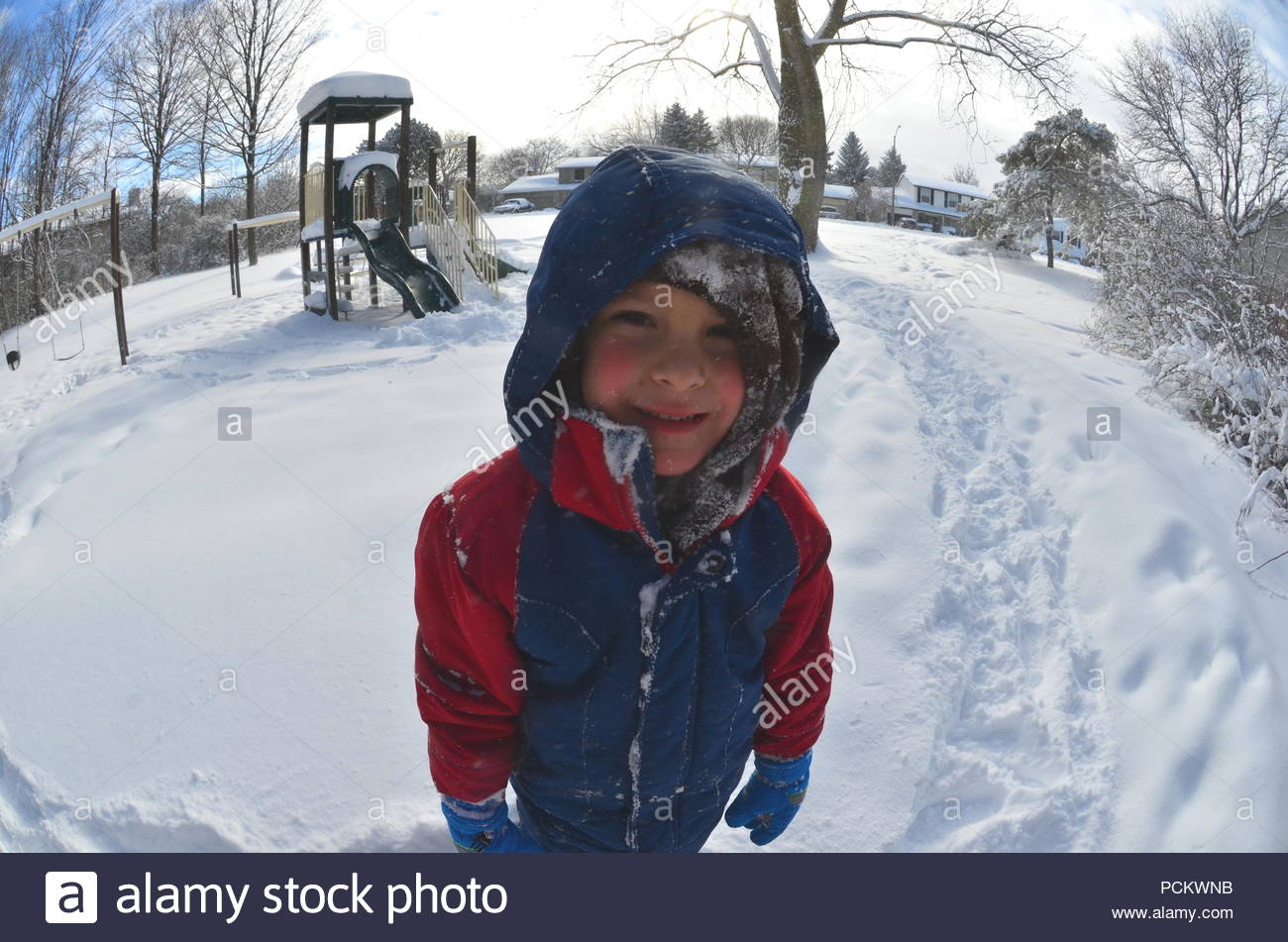 A happy Caucasian boy having fun and playing in the snow during frosty Canadian winter day - Stock Image