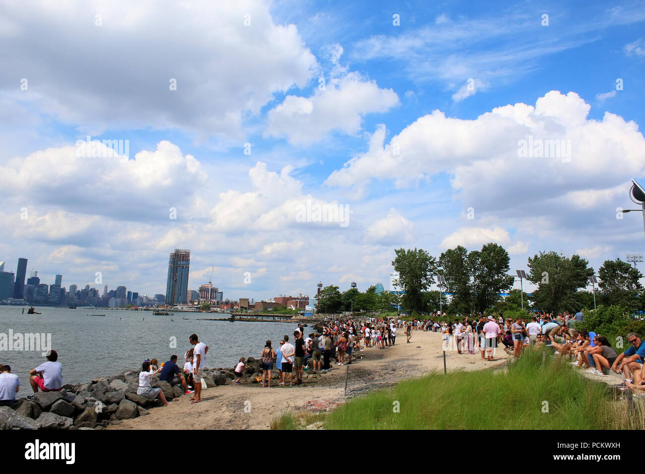 People resting on an East River Park beach during Smorgasburg in Williamsburg, Brooklyn on JULY 8th, 2017 in New York, USA. (Photo by Wojciech Migda) Stock Photo