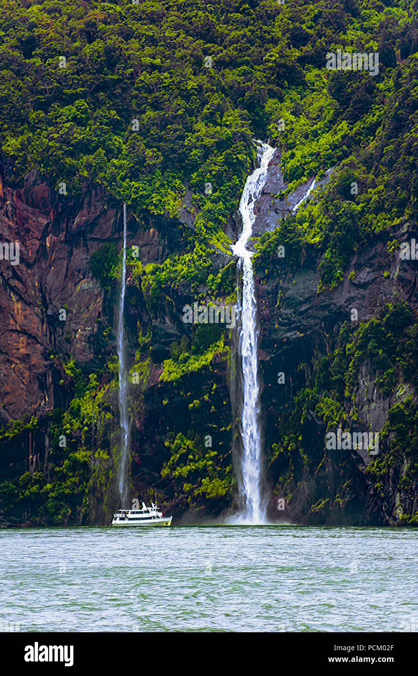 Tourist boat steers close to waterfalls plunging from mountain face covered with trees. - Stock Image
