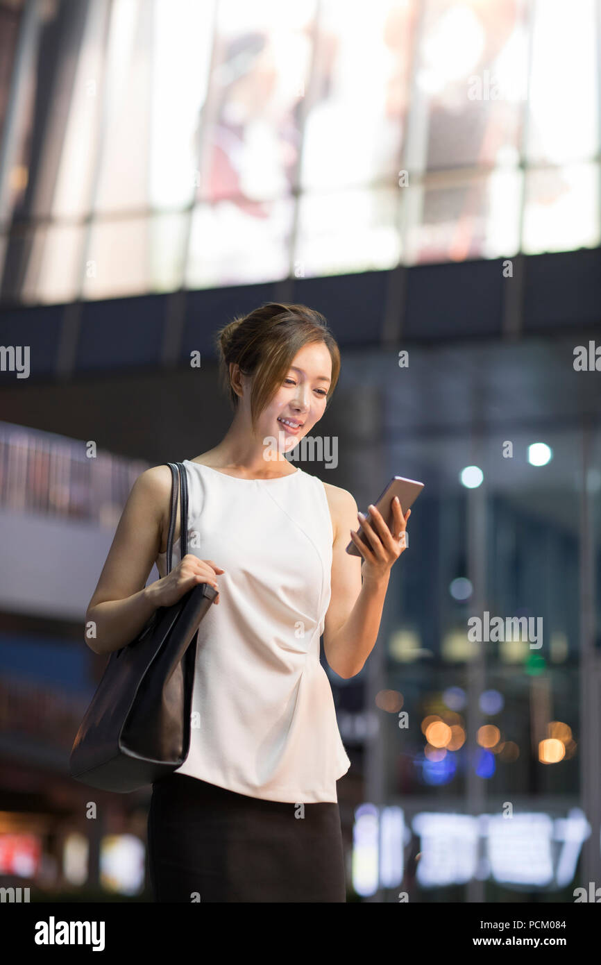 Cheerful young Chinese businesswoman using smart phone - Stock Image
