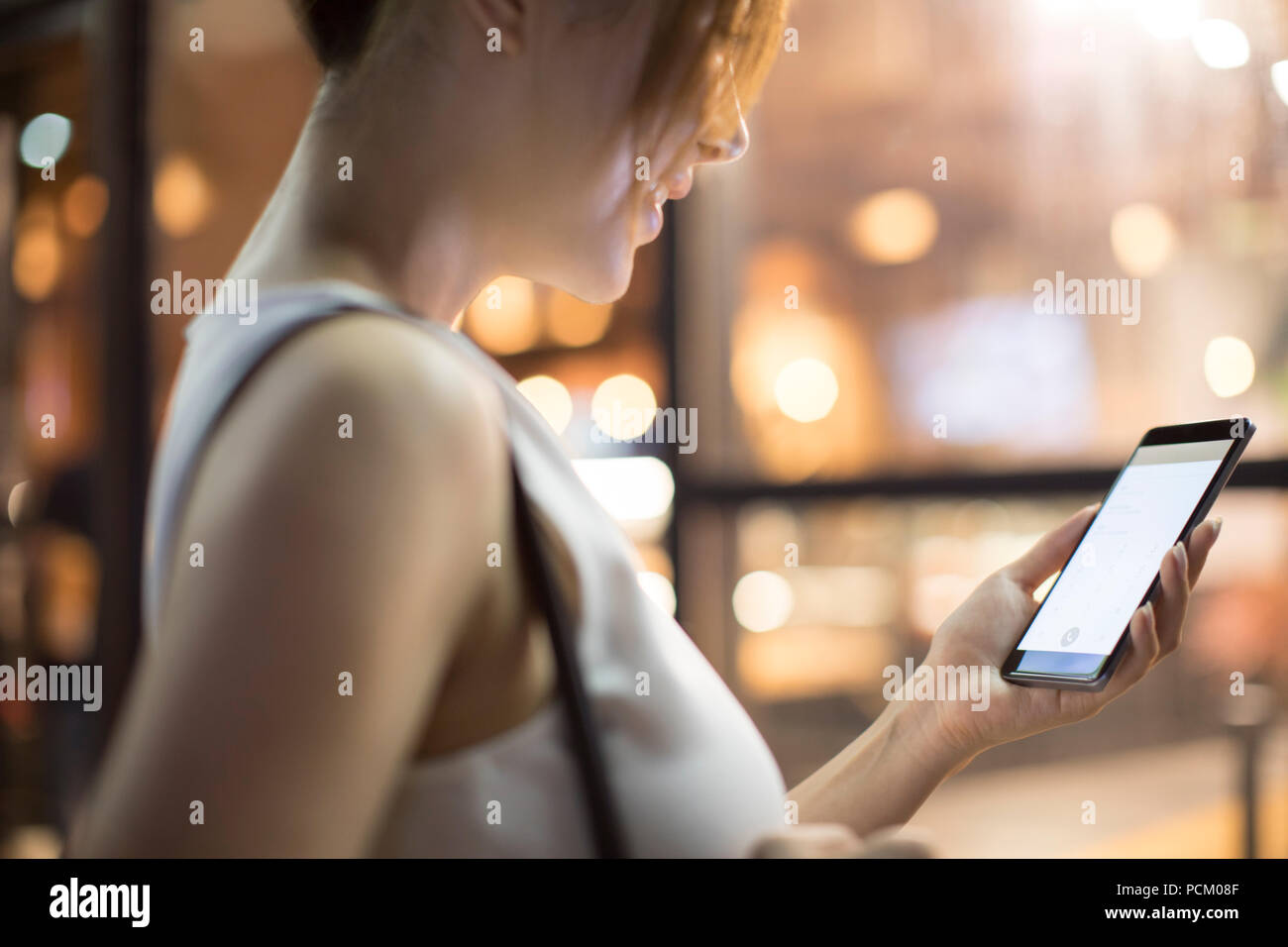 Cheerful young Chinese woman using smart phone - Stock Image