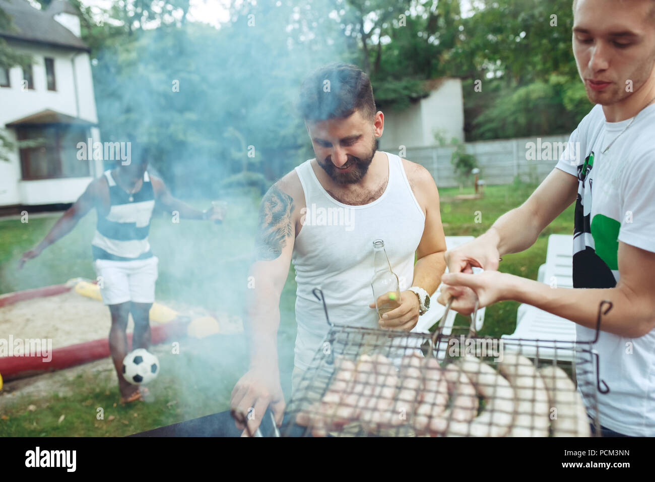 Group of friends making barbecue in the backyard. concept about good and positive mood with friends - Stock Image