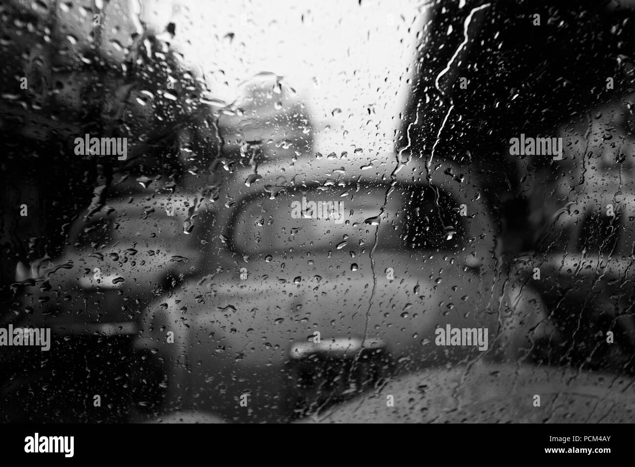 Rain drops on glass in focus out of focus cab in black white kolkata
