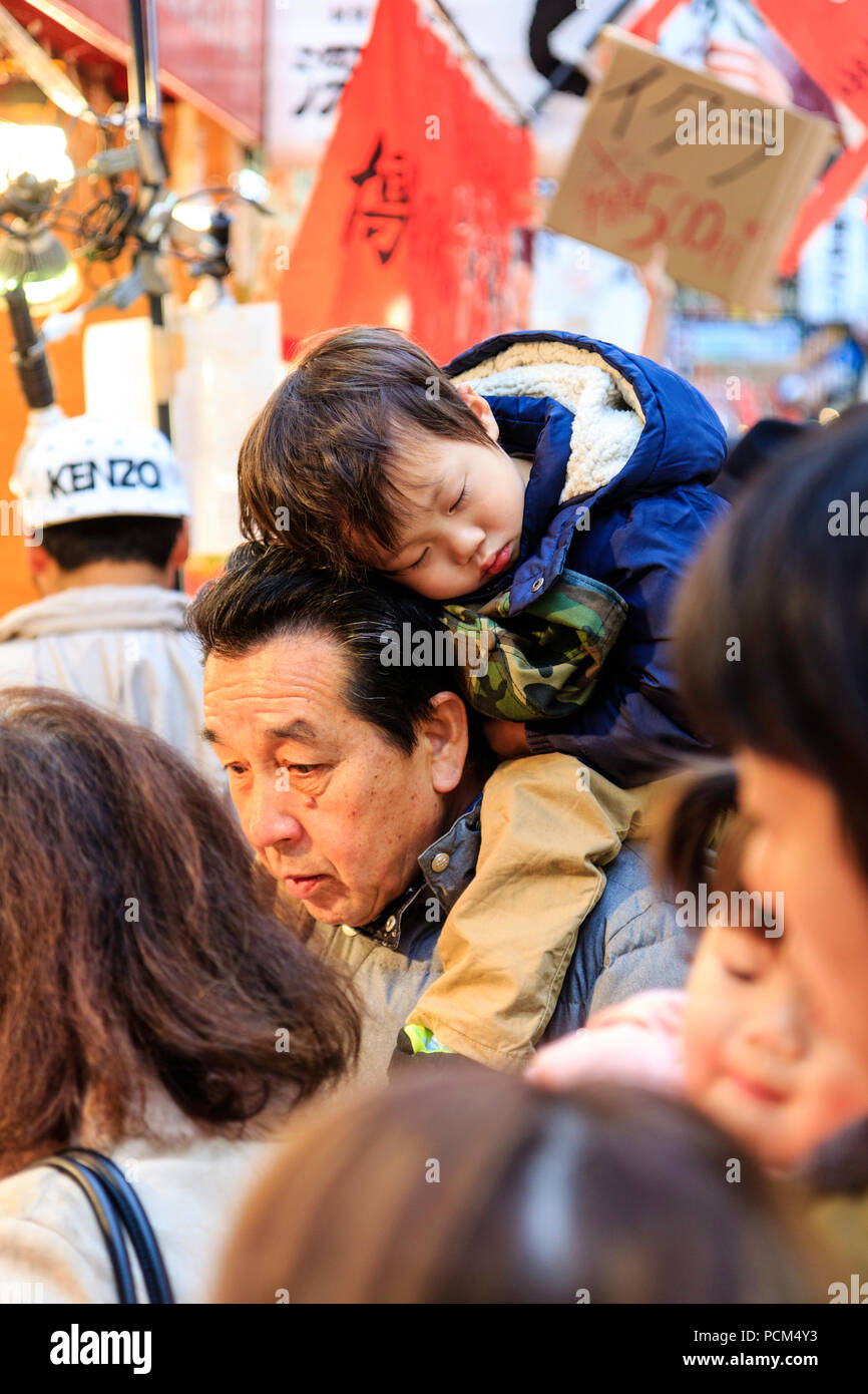 Japanese young child, boy, asleep on his father back as he is carried through a busy market in the day time. Candid shot at Kuromon Ichiba, Osaka. - Stock Image