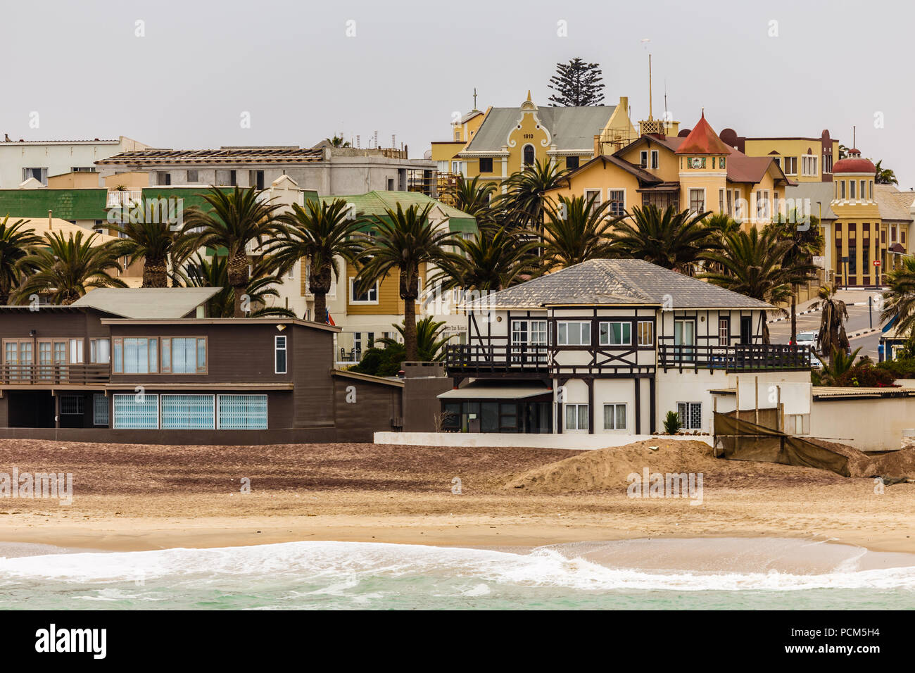 Coastline, palms and old blocks of Swakopmund German colonial town, Namibia - Stock Image