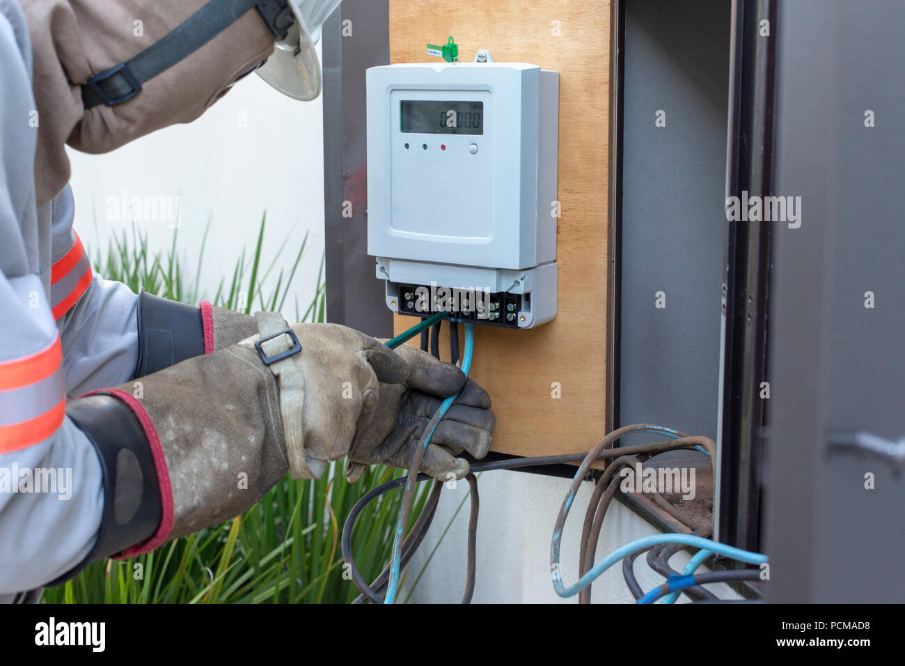 Solar electric meter. Technician installing a electric meters solar system. - Stock Image