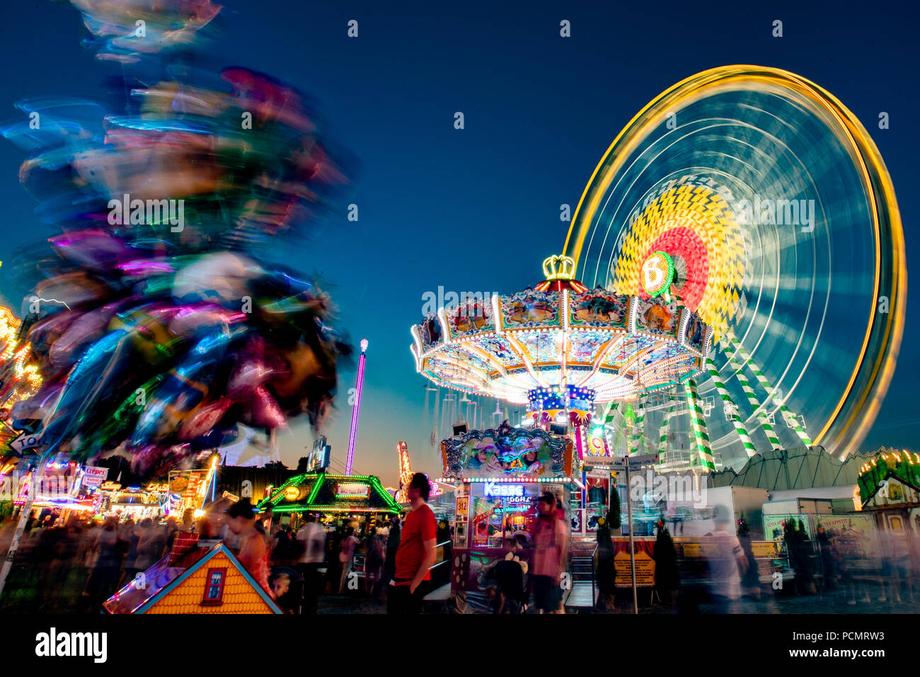 02 August 2018, Germany, Herne: A chain carousel rotates at the Cranger Kirmes. (long exposure) The folk festival with around 500 showmen is attended by more than four million people every year and is one of the largest folk festivals in Germany. Photo: Marcel Kusch/dpa - Stock Image