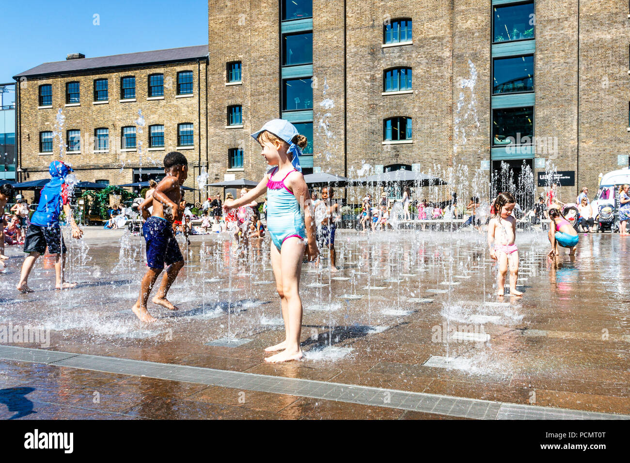 King's Cross, London, UK. 2nd August, 2018. As the British heatwave continues sun worshippers take to the canal and cool off in the fountains in Granary Square. Michael Heath/Alamy Live News - Stock Image