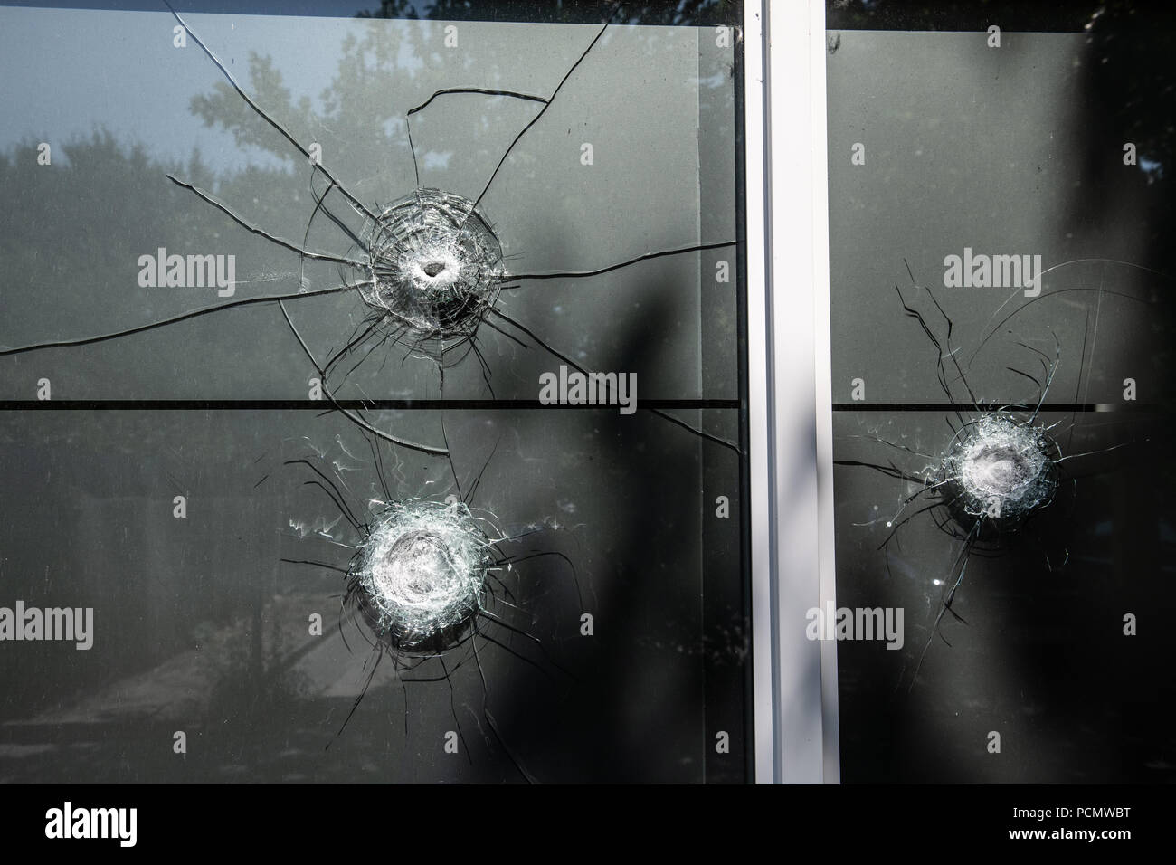 03 August 2018, Germany, Berlin: Bullet holes can be seen in the windows of the 'Chechen Cultural Centre' on Eichhorster Weg in the Maerkisches Viertel. There was a shooting the night before for as yet unknown reasons. Two men were seriously injured. Two suspects have been arrested. Photo: Paul Zinken/dpa - Stock Image