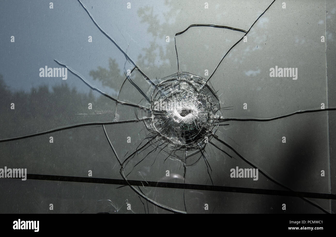 03 August 2018, Germany, Berlin: A bullet hole can be seen in the windows of the 'Chechen Cultural Centre' on Eichhorster Weg in the Maerkisches Viertel. There was a shooting the night before for as yet unknown reasons. Two men were seriously injured. Two suspects have been arrested. Photo: Paul Zinken/dpa - Stock Image