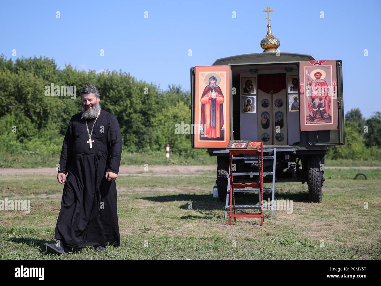 Russia. 03rd Aug, 2018. VLADIMIR REGION, RUSSIA - AUGUST 3, 2018: A Russian Orthodox priest near a mobile chapel, during the Open Water contest between pontoon bridge units at the 2018 International Army Games on the Oka River. Sergei Bobylev/TASS Credit: ITAR-TASS News Agency/Alamy Live News - Stock Image