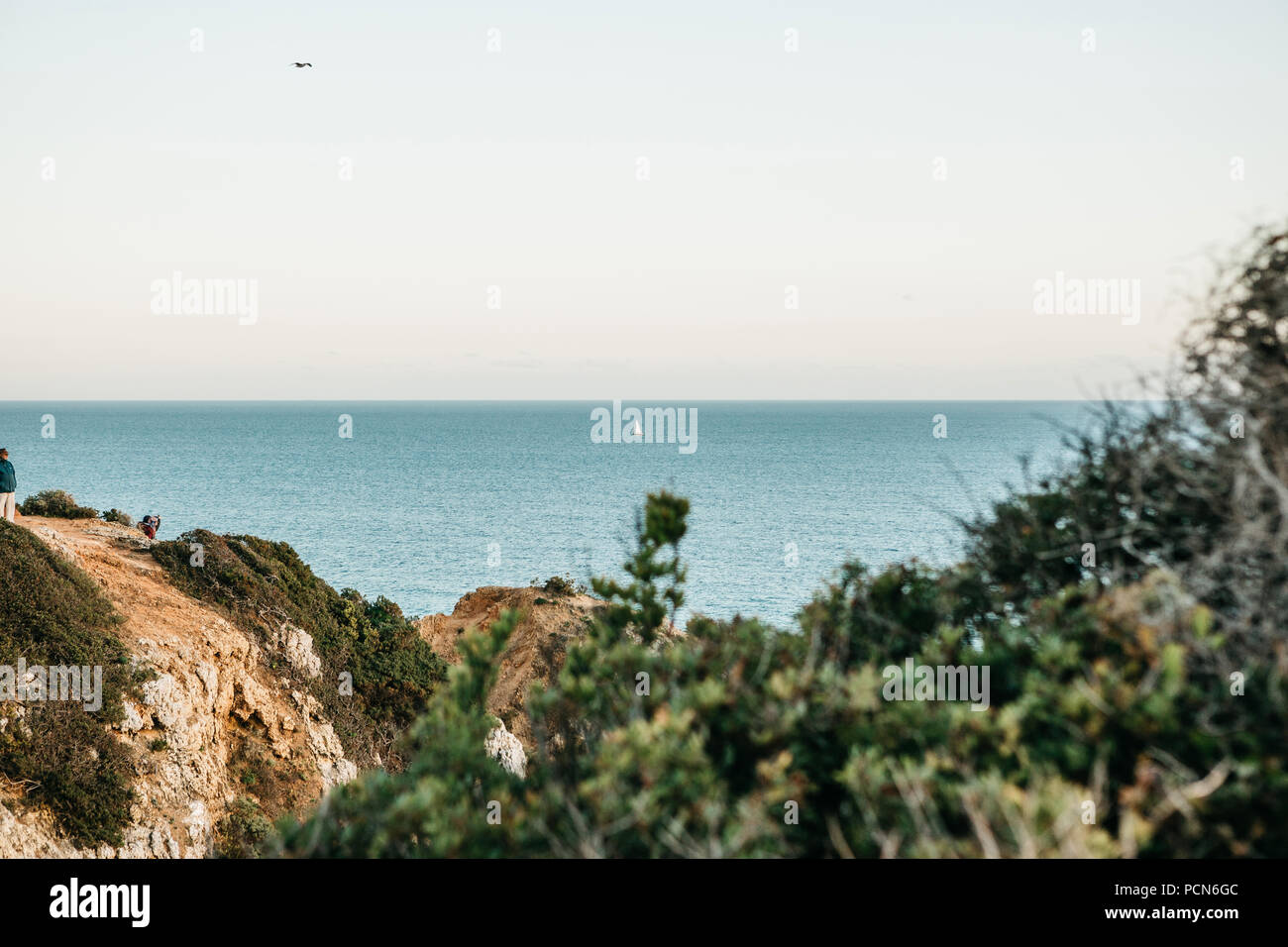 View of the Atlantic Ocean off the coast of Portugal and the sailboat floating in the distance. It is minimalistic. - Stock Image
