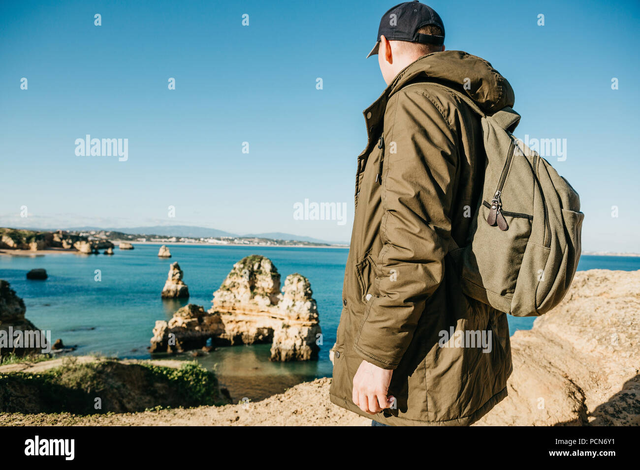 A tourist or traveler with a backpack admires the beautiful view of the Atlantic Ocean and the coast near the city called Lagos in Portugal. - Stock Image