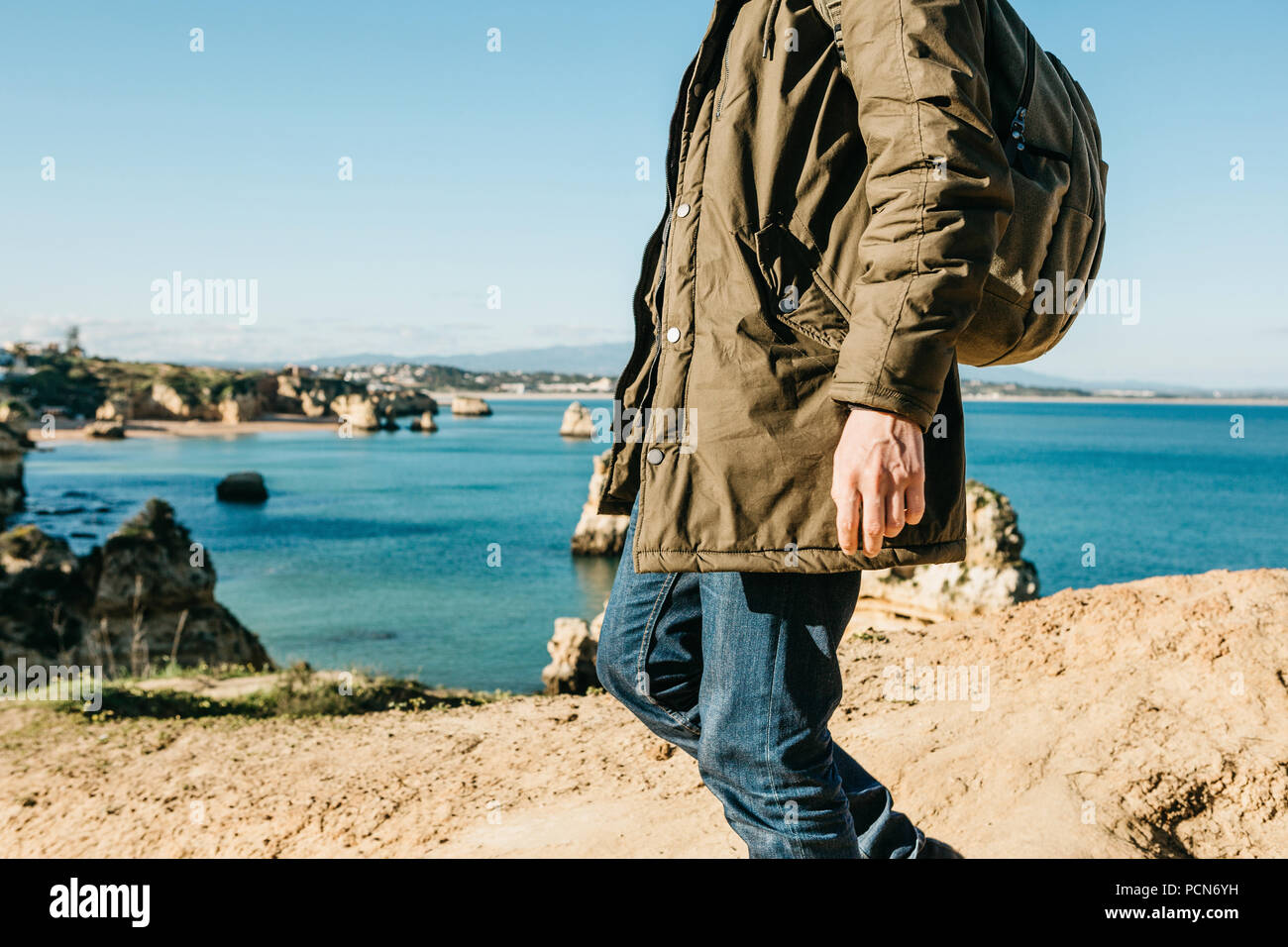 A tourist or traveler with a backpack walks along the coast of the Atlantic  Ocean and admires the beautiful view of the ocean near the city called  Lagos in ... bcc1dea4ad348