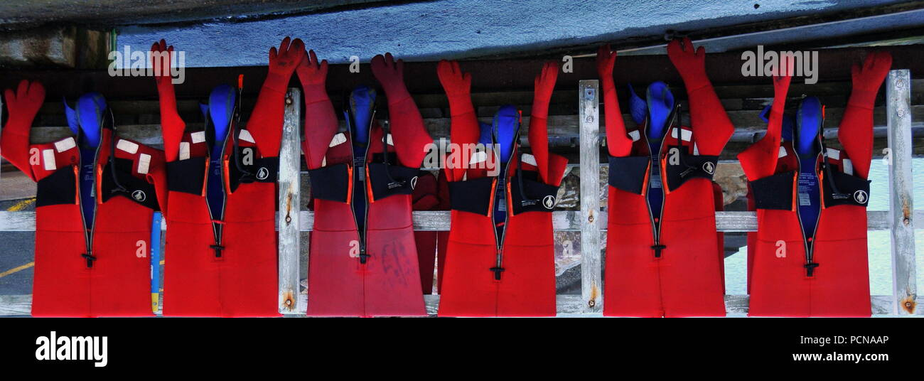 Drysuits of volunteer marine rescue crew drying off after practice - Stock Image