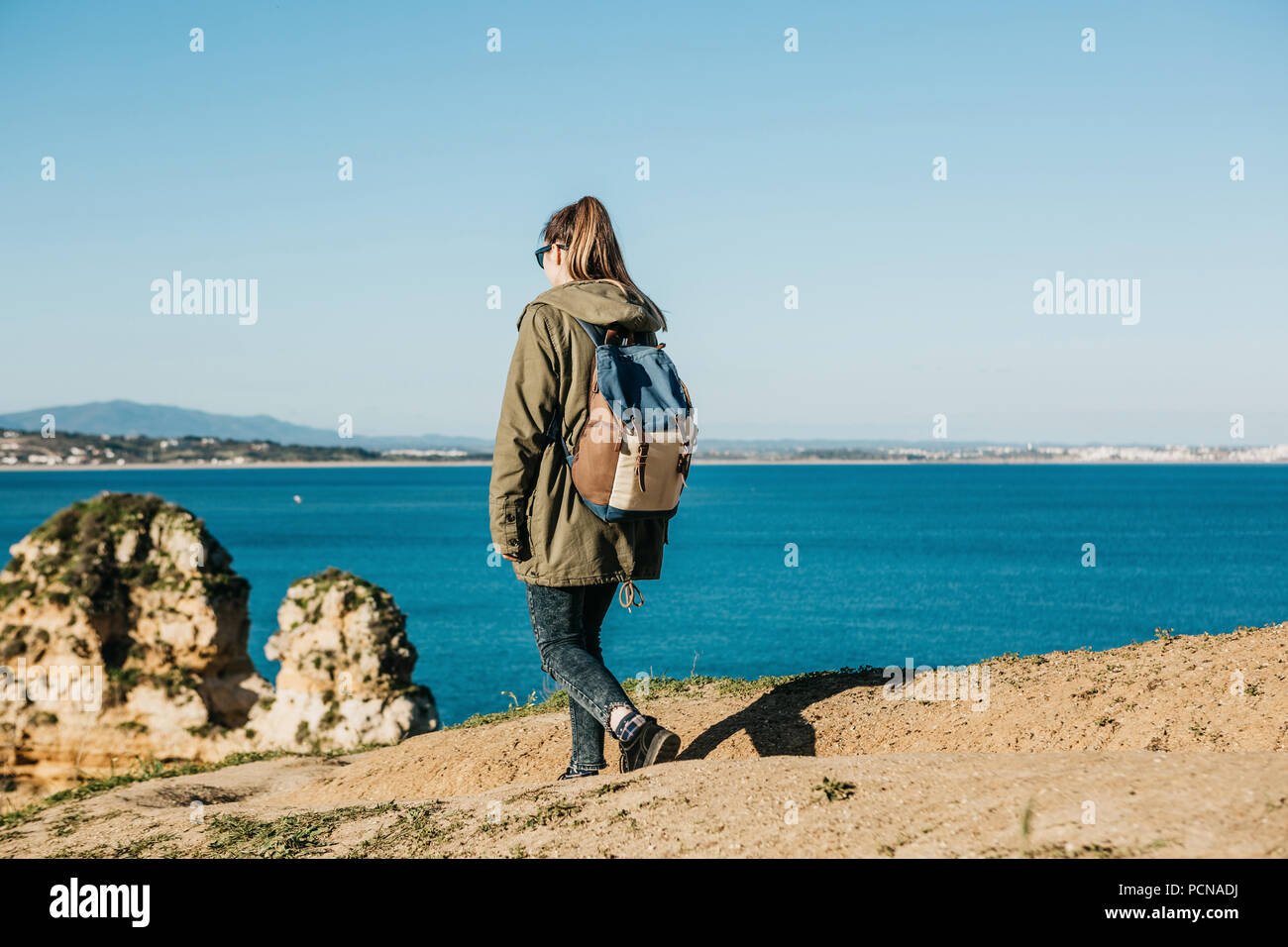 A girl tourist or traveler with a backpack walks along the rocky coast and admires the beautiful view of the Atlantic Ocean in Portugal Stock Photo