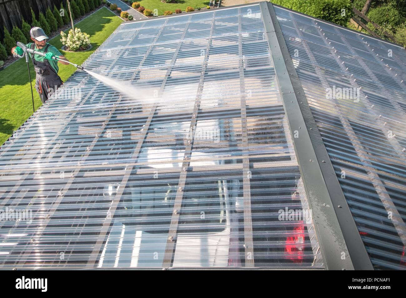 Caucasian Men in His 30s Cleaning Transparent Carport Garage Roof Using Pressure Washer. - Stock Image