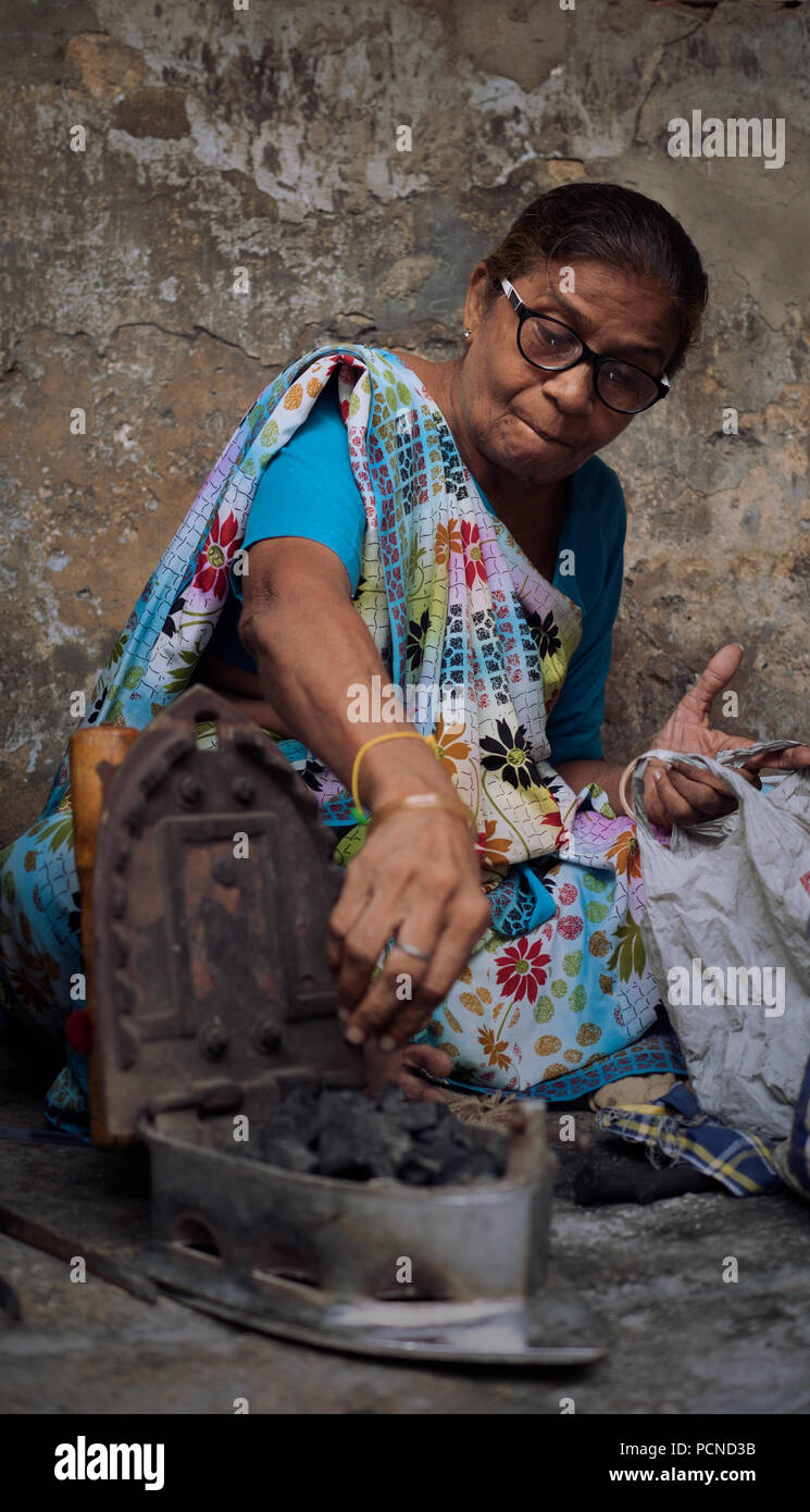 An ironing lady loads her coal heated iron - Stock Image