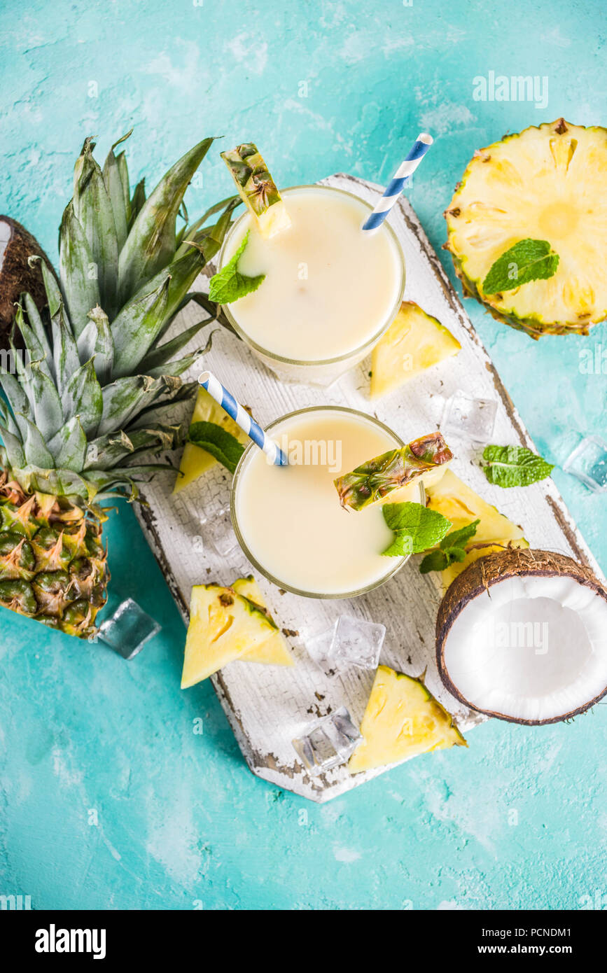 Refreshing summer drink, homemade pina colada cocktail, on a light blue background, with pieces of pineapple, coconut, ice and mint leaves, copy space Stock Photo