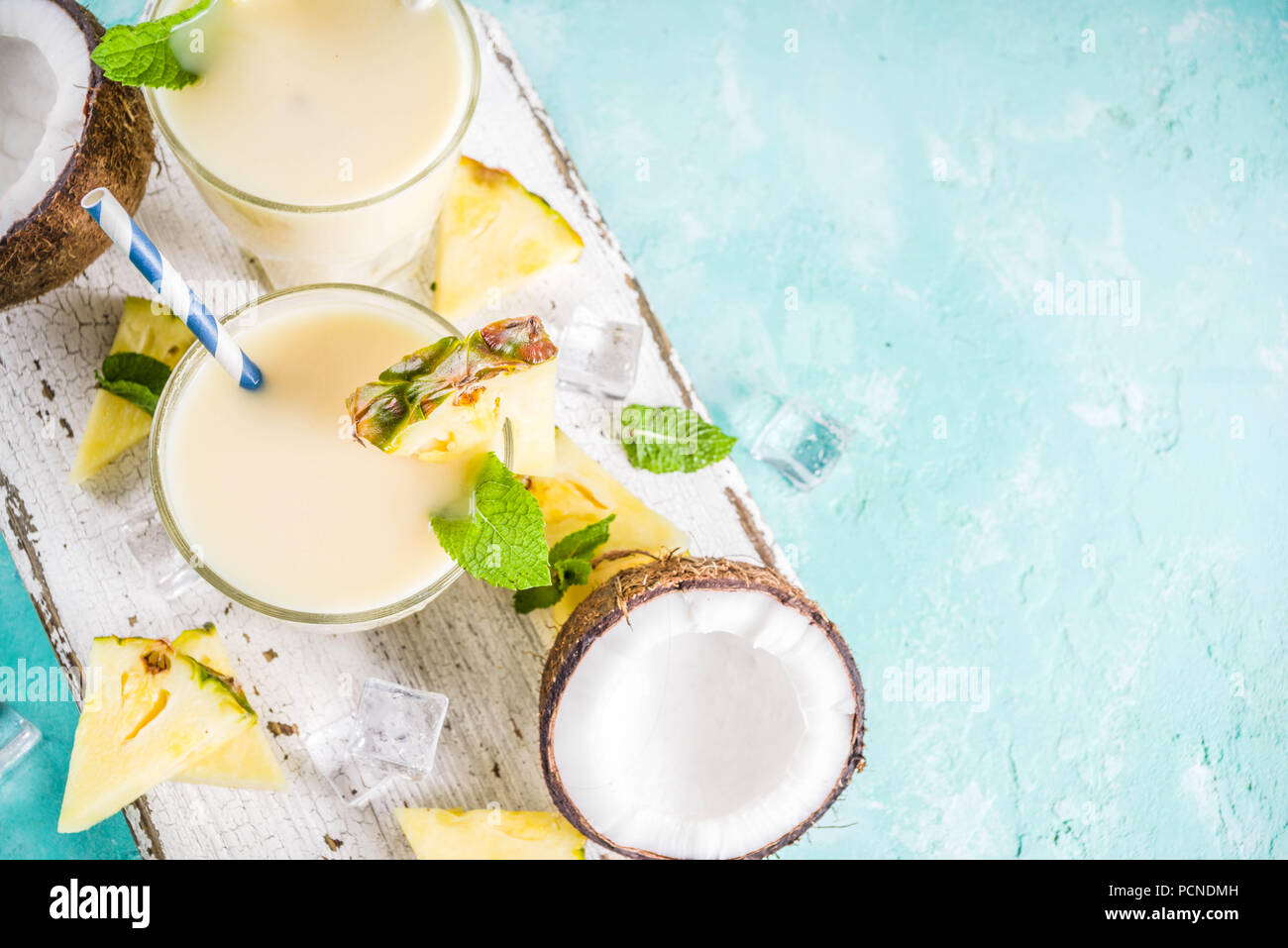 Refreshing summer drink, homemade pina colada cocktail, on a light blue background, with pieces of pineapple, coconut, ice and mint leaves, copy space - Stock Image