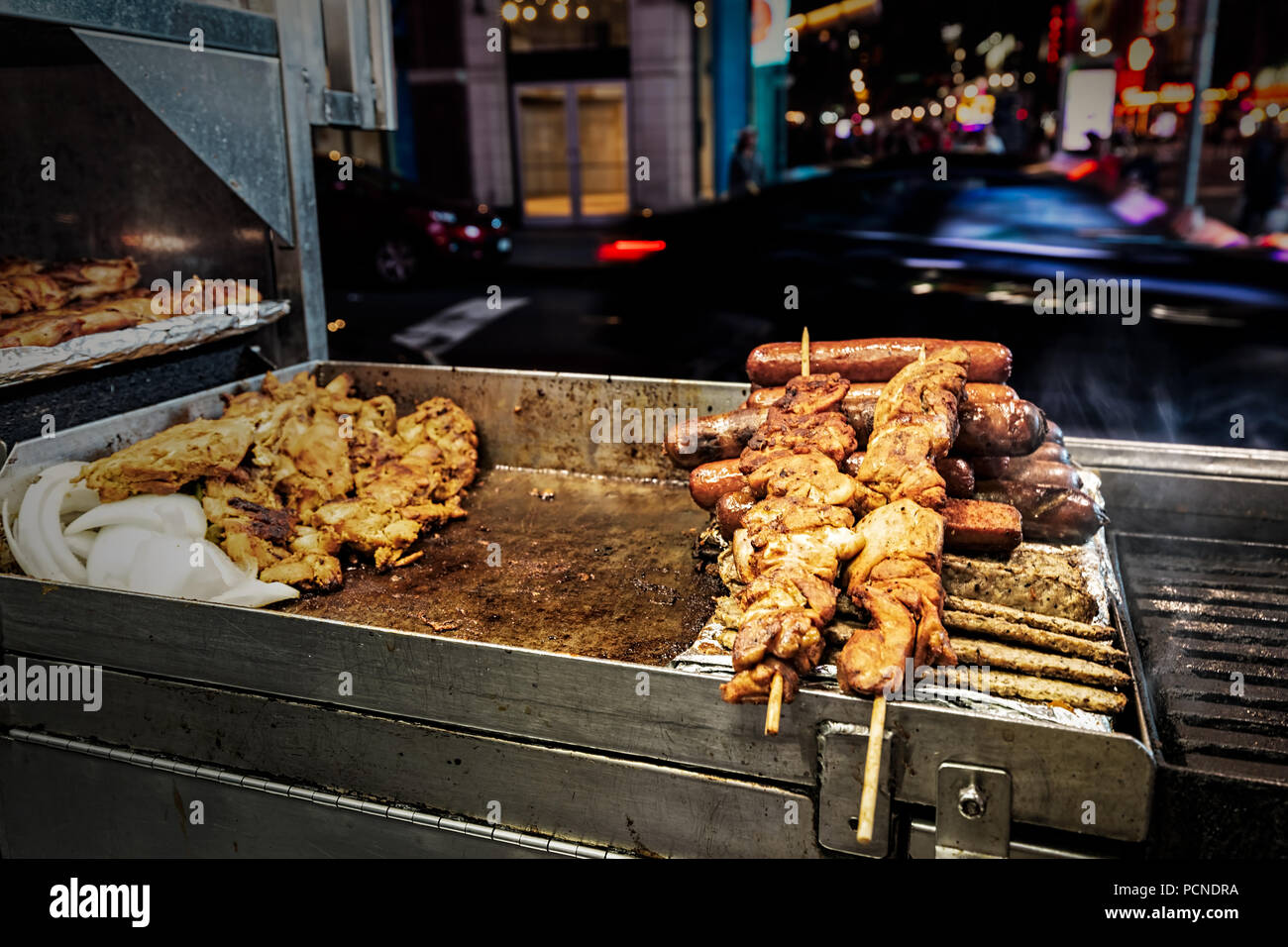 A grill at a food stand in New York City with chicken, sausages and kebabs on skewers. - Stock Image