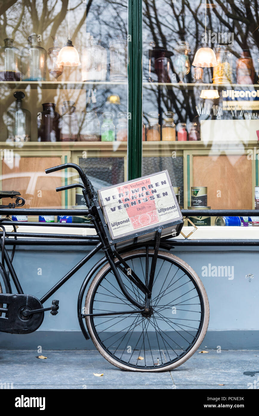 Old Dutch 'sit up and beg' bicycle leaning against a hardware shop window in Delft, Netherlands - Stock Image