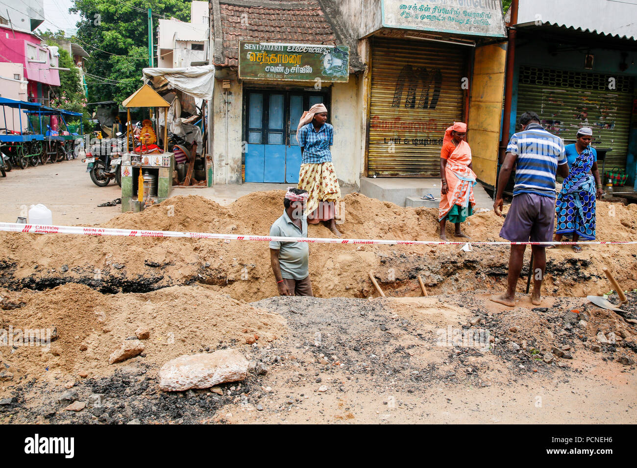 PONDICHERY, PUDUCHERY, INDIA - SEPTEMBER 04, 2017. Unidentified workers with shovels in a trench, dig trenches along the road. Concept of hard work in Stock Photo